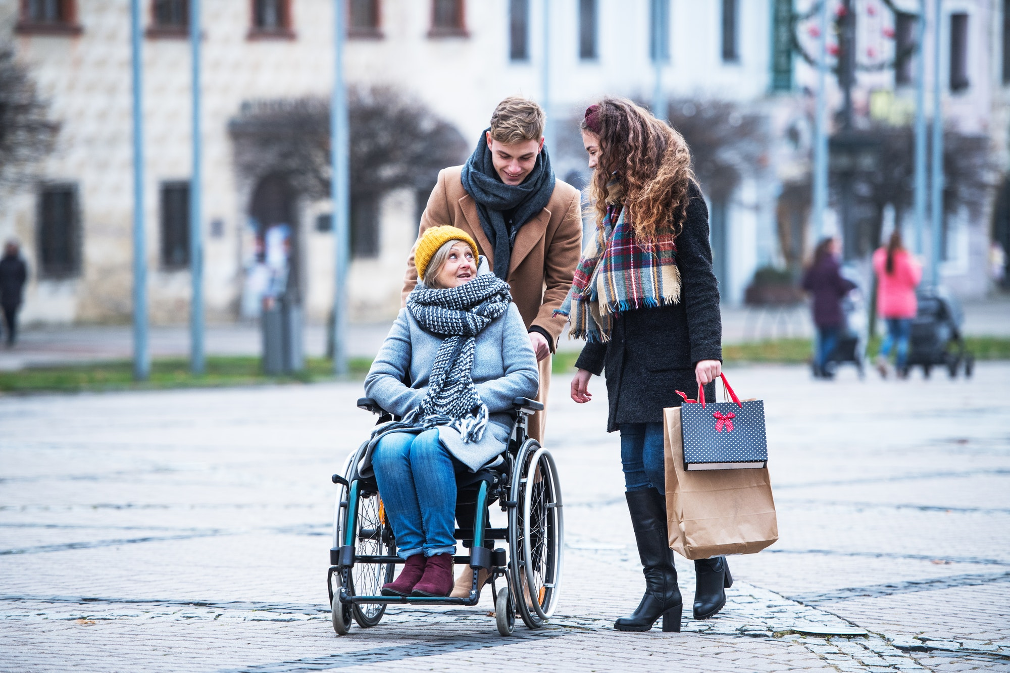 Teenagers and senior grandmother in wheelchair walking down the street in winter.